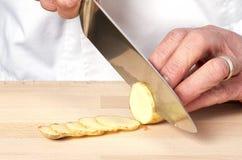 Chefhände, die Kartoffel hacken lizenzfreie stockbilder