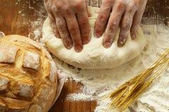 Chefhände mit Teig und selbst gemachtes natürliches organisches Brot und Mehl Stockbild