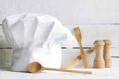 Chefhut und hölzerne Küchengeschirrlebensmittelzusammenfassung Lizenzfreie Stockfotos