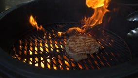 Chefkoch das saftige große Fleischsteak auf dem runden Grill, durch den das Feuer glüht stock video footage
