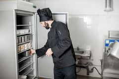 Chefkoch, der Lebensmittel vom Kühlschrank erhält stockfotografie