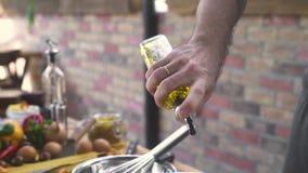 Chefkoch, der Olivenöl von der Flasche beim Kochen des Salats am Ziegelsteinhintergrund gießt Männliche Hand, die Olivenölflasche stock footage