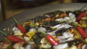 Chefkoch, der spanische Paella mit glühenden Pfeffern und frischen Meeresfrüchten im Wannenabschluß oben kocht Vorbereitung tradi