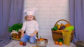 Chefmädchen, welches das Kochen mit gesundem Lebensmittel in der Küche spielt stock video
