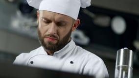 Chefmannporträt an der Berufsküche Chef, der Nahrung in der Zeitlupe kocht stock footage