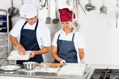 Chefs Baking At Kitchen Counter. Young male chef with female colleague baking in commercial kitchen Stock Photos