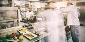 Chefs busy at work. In professional kitchen stock photography