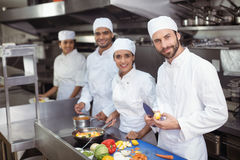 Chefs chopping vegetables on chopping board in the commercial kitchen stock photo