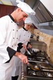 Chefs cooking. Young happy professional chefs cooking in kitchen Stock Photography