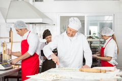 Chefs Cooking Pasta Together In Kitchen Royalty Free Stock Photography