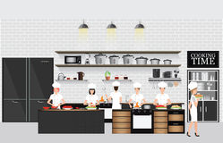 Chefs cooking at the table in restaurant kitchen interior. Chefs cooking at the table in restaurant kitchen interior with kitchen shelves and cooking utensils Royalty Free Stock Image