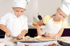 Chefs d'enfant découpant des ingrédients en tranches sur le hachoir Images libres de droits