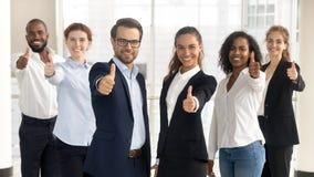 Chefs de file des affaires avec des employ?s montrant des pouces vers le haut de regarder la cam?ra images stock