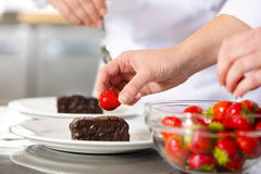 Chefs decorates dessert cake with chocolate sauce in kitchen Royalty Free Stock Image