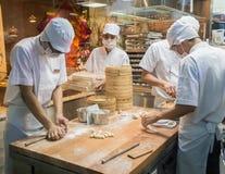 Chefs in den weißen Uniformen kochten Gericht des Teigs in einer sauberen Küche, Singapur Stockbild