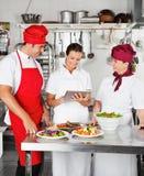 Chefs, die Digitalrechner in der Küche verwenden Stockfotos