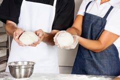 Chefs, die Teig in der Küche darstellen Lizenzfreies Stockbild