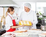 Chefs Discussing While Holding Pasta Tray In Royalty Free Stock Photo