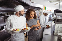 Chefs discussing menu on clipboard. In commercial kitchen Royalty Free Stock Photo