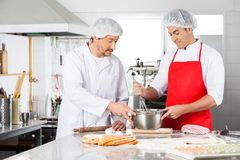 Chefs Discussing While Preparing Ravioli Pasta In Royalty Free Stock Photography