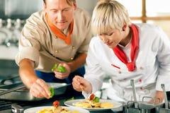 Chefs in einem Gaststätte- oder Hotelküchekochen Stockfotos