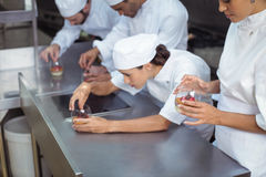 Chefs finishing dessert in glass at restaurant Royalty Free Stock Photography