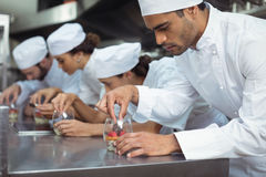 Chefs finishing dessert in glass at restaurant. Attentive chefs finishing dessert in glass at restaurant Royalty Free Stock Images