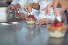 Chefs finishing dessert in glass at restaurant Stock Photography