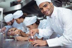 Chefs finishing dessert in glass at restaurant Royalty Free Stock Photo