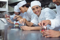 Chefs finishing dessert in glass at restaurant. Smiling chefs finishing dessert in glass at restaurant Royalty Free Stock Photography