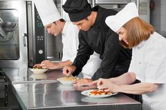 Chefs Garnishing Dishes On Counter Royalty Free Stock Images