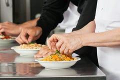 Chefs garnissant des plats de pâtes Images libres de droits