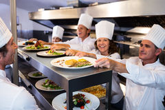 Chefs handing dinner plates through order station Royalty Free Stock Photography