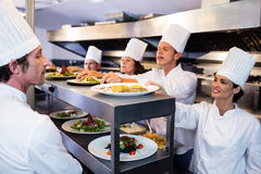 Chefs handing dinner plates through order station. In the commercial kitchen Stock Photo