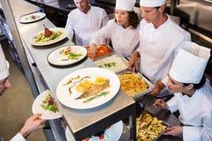 Chefs handing dinner plates through order station Stock Image