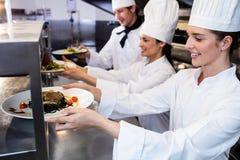 Chefs handing dinner plates through order station Stock Photo