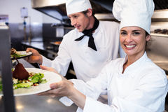 Chefs handing dinner plates through order station. In the kitchen Stock Photography