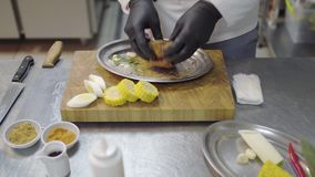 Chefs hands in black latex gloves rubs a piece of veal in the metal plate, marinating meat. Kitchen table with. Kitchenware and ingredients stock footage