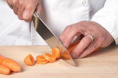 Chefs hands chopping carrot Stock Images