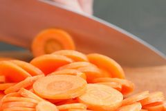 Chefs hands chopping carrot on wooden board Royalty Free Stock Photography