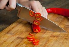 Chefs hands chopping chili pepper Stock Photo
