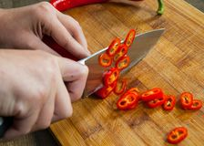 Chefs hands chopping chili pepper Stock Photos