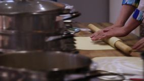 Chefs hands unrolling dough with a rolling pin in. Chefs hands unrolling dough with  rolling pin in kitchen stock video