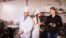 Chefs and handsome waiter working. Cheerful chefs and handsome waiter working at eating house Royalty Free Stock Photo