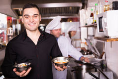 Chefs and handsome waiter working. At eating house Stock Images