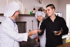 Chefs and handsome waiter working Stock Photography