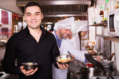 Chefs and happy waiter working. At eating house Stock Photos