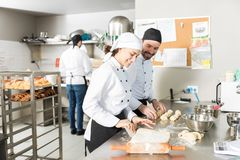 Chefs Having Fun While Making Bread Dough. Happy bakers making dough for bread pastries in restaurant kitchen stock photos