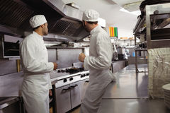Chefs interacting with each other in kitchen. At restaurant Stock Photos