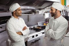 Chefs interacting with each other in kitchen. At restaurant Stock Image